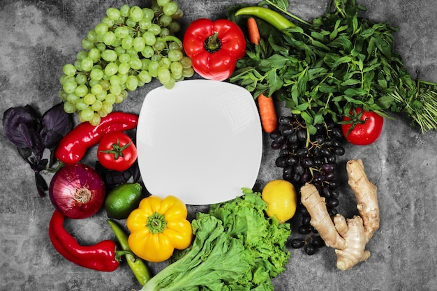 Druiven, paprika, greens, citroen, tomaat, gember en witte plaat op marmeren achtergrond. Gratis Foto