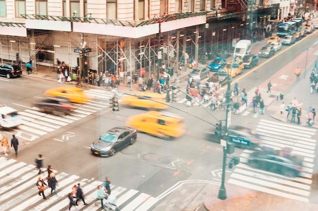 Druk kruispunt vol met auto's en mensen Gratis Foto