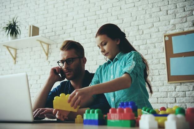 Drukke alleenstaande vader werkt met laptop Premium Foto