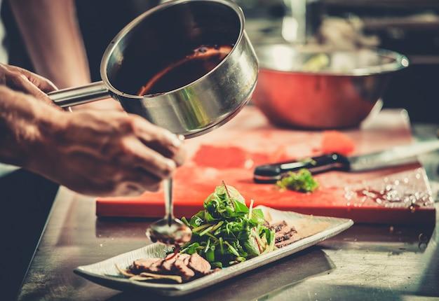 Drukke chef-kok aan het werk in de restaurantkeuken Premium Foto