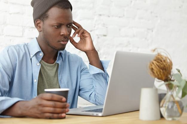Drukke man met donkere huid serieus op zoek in laptopcomputer terwijl het lezen van nieuws online, papieren beker met koffie houden, rust in de cafetaria. knap mannetje die elektronisch boek op computer lezen Gratis Foto