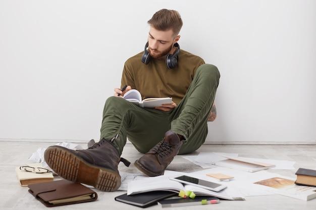 Drukke mannelijke student draagt vrijetijdskleding en laarzen, schrijft aantekeningen en is betrokken bij het studeren voor de sessie Gratis Foto