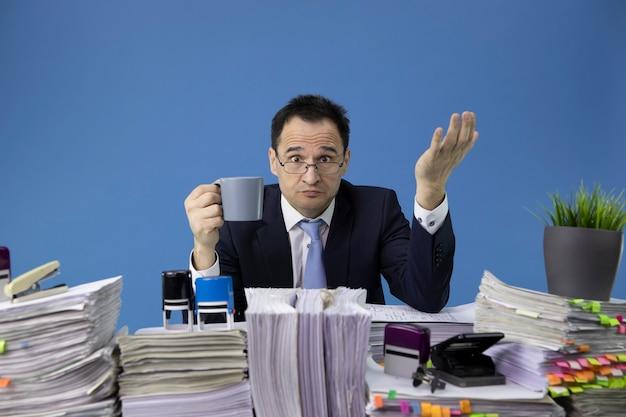Drukke overwerkte man met pet van koffie zittend aan tafel met stapel papieren in kantoor Premium Foto
