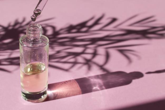 Druppel valt uit een pipet in een glazen fles met cosmetische olie of serum Premium Foto