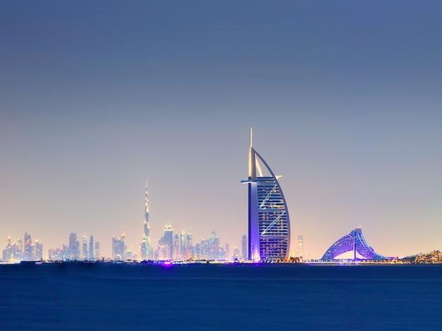 Dubai - 17 november 2017: skyline van dubai 's nachts met burj al arab op voorgrond verenigde arabische Premium Foto