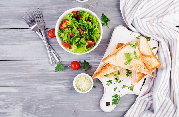 Dubbeldekker panini met ham, kaas en salade. bovenaanzicht lekker ontbijt Premium Foto