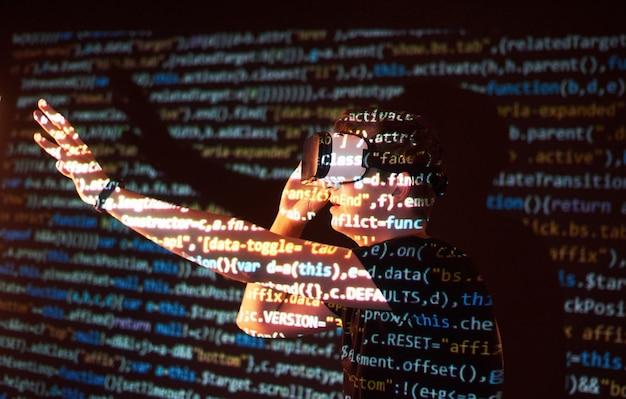 Dubbele blootstelling van een blanke man en een virtual reality vr-headset is vermoedelijk een gamer of een hacker die de code kraken in een beveiligd netwerk of server, met coderegels Gratis Foto