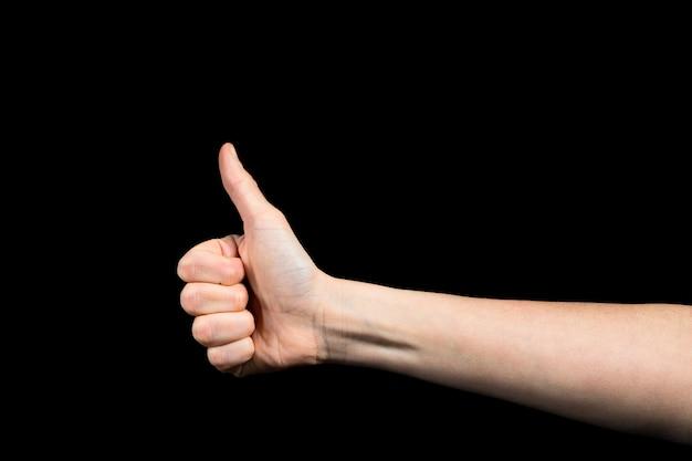 Duim omhoog van kaukasische vrouwelijke hand op zwarte achtergrond Premium Foto