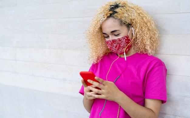 Duizendjarig meisje dat mobiele telefoon met behulp van terwijl het dragen van gezichtsmasker tijdens coronavirusuitbraak Premium Foto