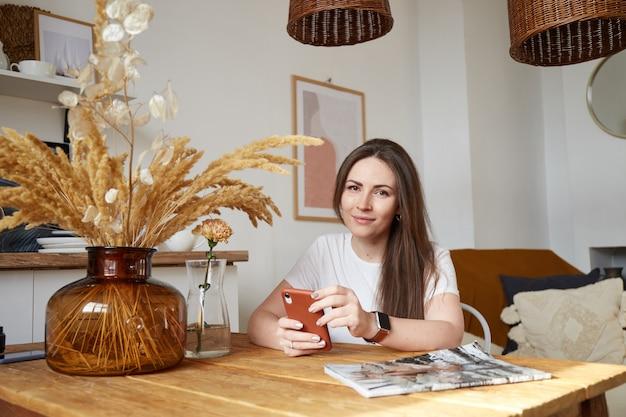 Duizendjarige vrouw die werkt in de keuken van de ecostijl. trendy kleuren. natuurlijk licht. freelancer Premium Foto
