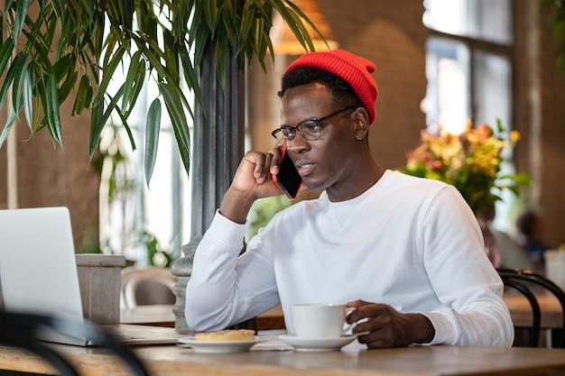 Duizendjarige zwarte man praten op mobiele telefoon Premium Foto