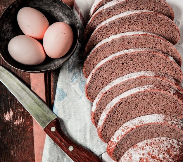 Dun gesneden zwart brood, mes en eierkom op witte handdoek. Gratis Foto