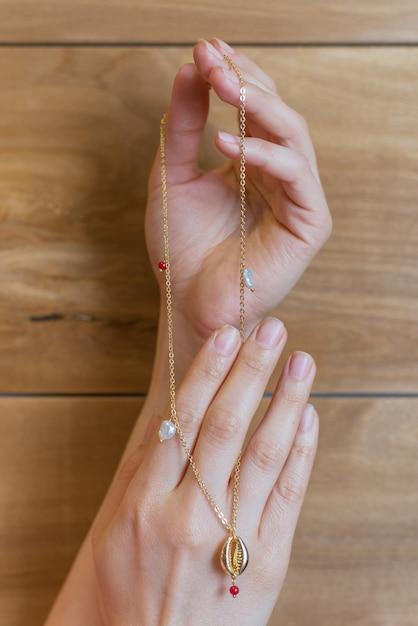 Dure mooie sieraden met parels en een zeeschelp van goud in de handen van een meisje met een natuurlijke manicure op een houten muur Premium Foto