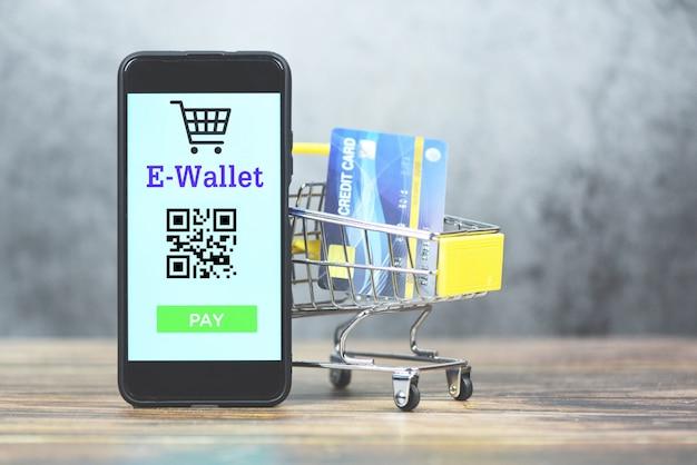 E-portemonnee-app op telefoon met creditcard in winkelwagen technologie betalen - mobiel betalen online winkelen concept Premium Foto