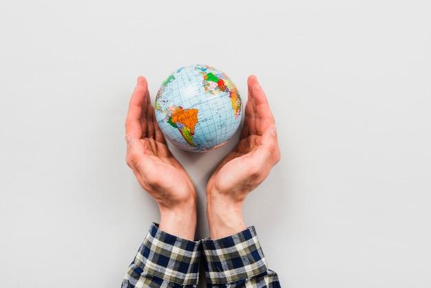 Earth globe omgeven door handen Gratis Foto