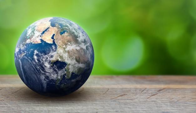 Earth planet bol op groene bladeren achtergrond. ecologie en milieuzorgconcept. greenpeace en earth day-thema. elementen van deze afbeelding geleverd door nasa Premium Foto