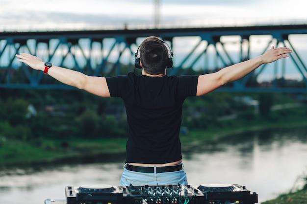 Echte dj speelt muziek op een feestje, staat met zijn rug en duwt zijn armen naar de zijkanten in de open lucht Premium Foto