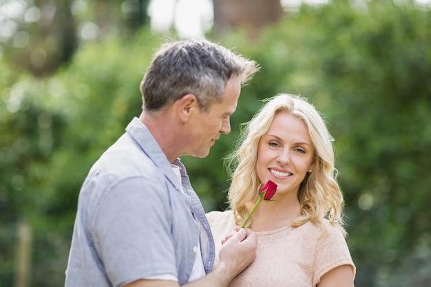 Echtgenoot die een roos aan vrouw aanbiedt buiten in het bos Premium Foto