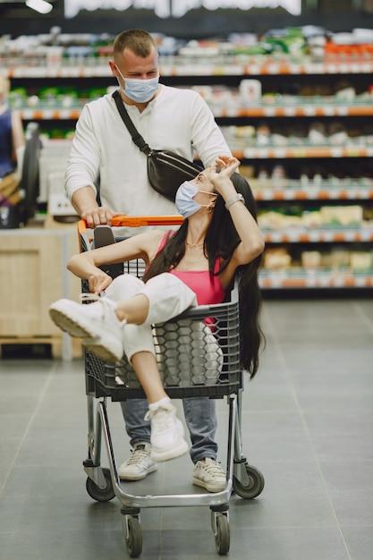 Echtpaar in een supermarkt. dame in een medisch masker. mensen maken parchases. Gratis Foto