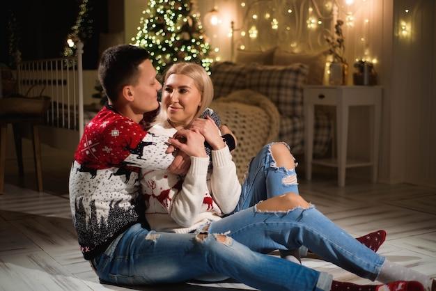 Echtpaar in gebreide truien in de buurt van de kerstboom. man en vrouw in kerst interieur kamer. Premium Foto