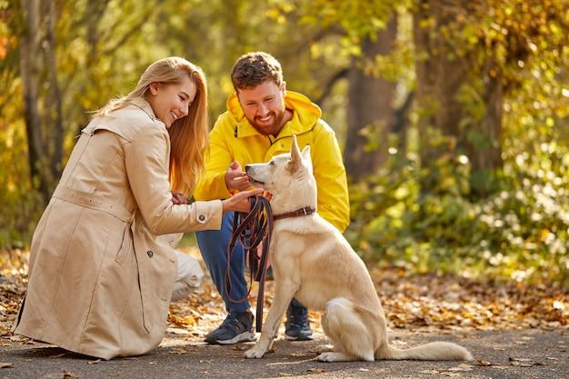 Echtpaar met hond wandelen. positieve blanke paar genieten van tijd  doorbrengen met hond in het bos | Premium Foto