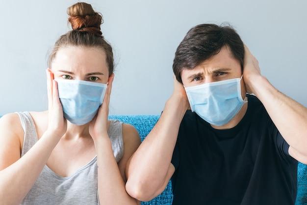 Echtpaar met medische gezichtsmaskers die hun hoofd met hun handen houden Premium Foto