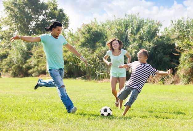 Echtpaar met zoon spelen met voetbal Gratis Foto