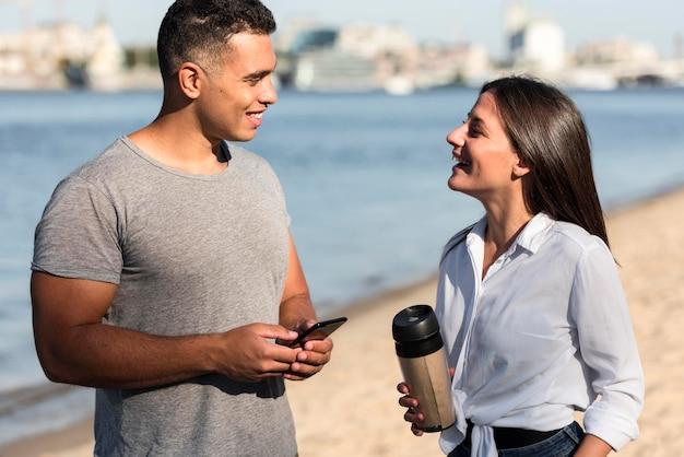 Echtpaar praten op het strand Gratis Foto