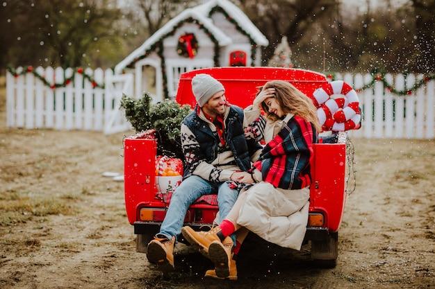 Echtpaar zit in de auto met kerstdecor sneeuwt Premium Foto