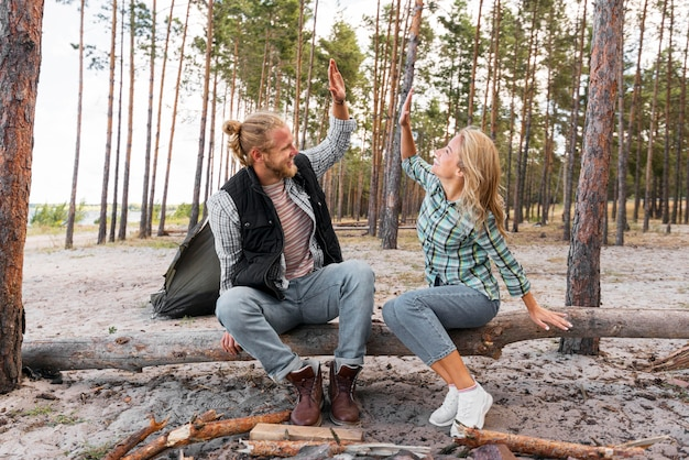 Echtpaar zittend op een boomstam high five Premium Foto