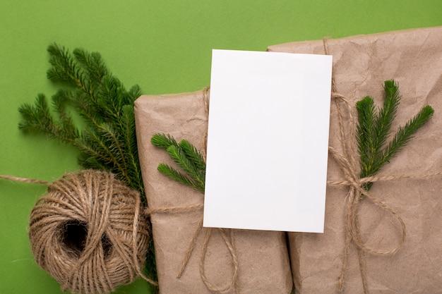 Eco aanwezig en kaart met groene planten in ambachtelijk papier op een groen oppervlak Premium Foto