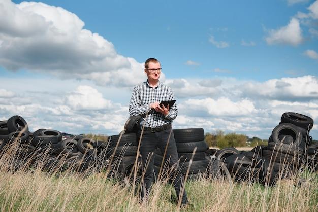 Eco-activist op de stortplaats van gebruikte autobanden berekent milieuschade Premium Foto