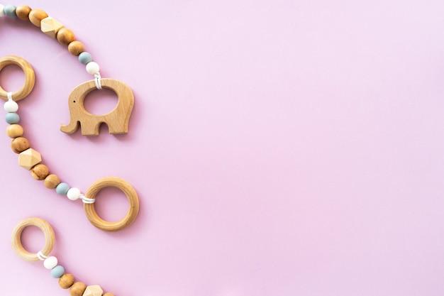 Eco-vriendelijk houten kinderspeelgoed op een roze achtergrond, bovenaanzicht, platte lay-out, kopie ruimte Premium Foto