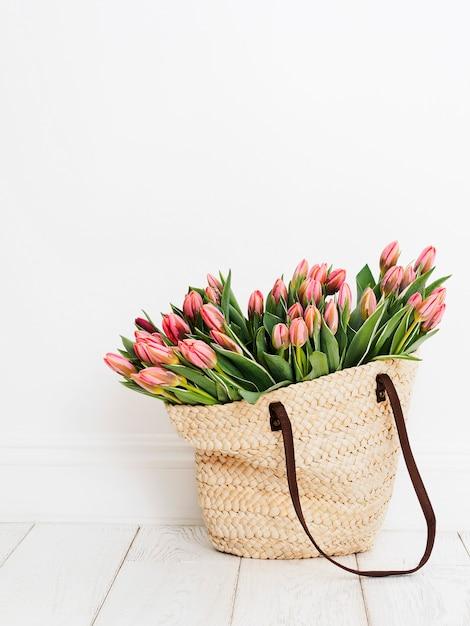 Eco-vriendelijke boodschappentas geweven met tulpen voor een witte muur achtergrond Premium Foto