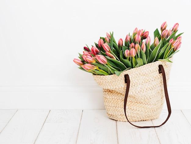 Eco-vriendelijke boodschappentas geweven met tulpen voor een witte muur Premium Foto