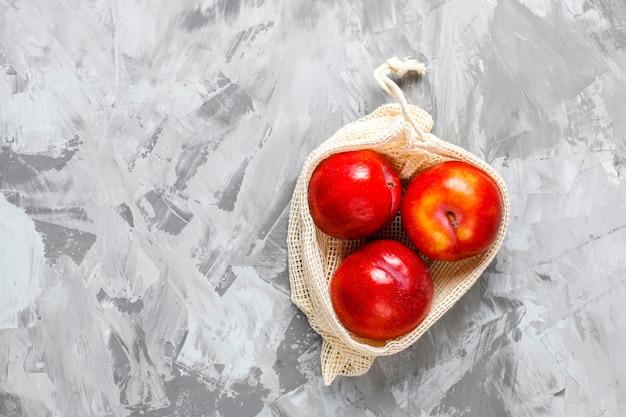 Eco-vriendelijke eenvoudige beige katoenen boodschappentassen voor het kopen van groenten en fruit met zomerfruit. Gratis Foto