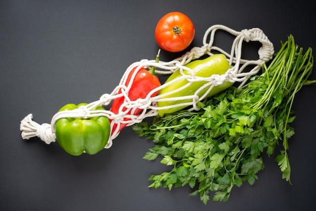 Eco-vriendelijke tas met verse groenten op zwart. bovenaanzicht Premium Foto