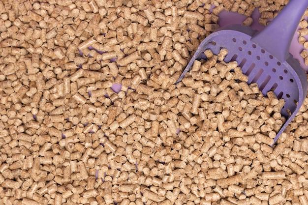 Ecologische houtvuller voor kattenbakvulling en kleine dieren cavia's,  konijnen, schildpadden. close-up en paarse uil, toilet, achtergrond |  Premium Foto