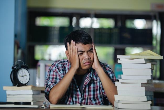 Educatief concept: vermoeide student in een bibliotheek Gratis Foto