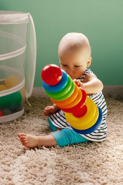 Educatief logisch speelgoed voor kinderen. kind verzamelt gekleurde piramide. spellen voor de ontwikkeling van het kind. Premium Foto