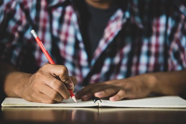 Educatief thema: close-up student schrijft in een klaslokaal. Gratis Foto