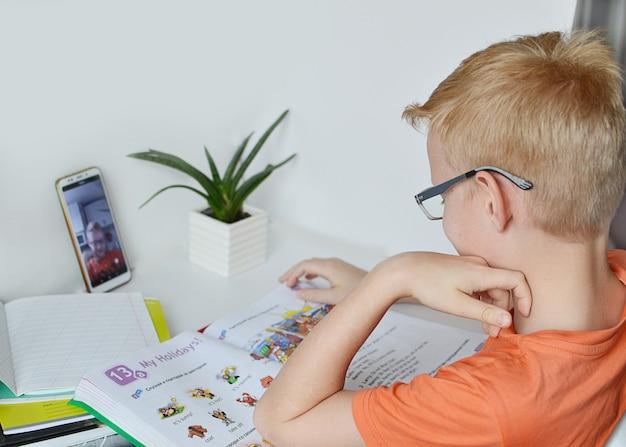 Een 9-jarige jongen houdt zich bezig met afstandsonderwijs, online les thuis, sociale afstand tijdens quarantaine. zelfisolatie. concept online onderwijs, thuisonderwijs Premium Foto