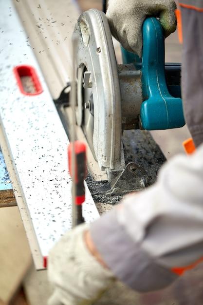 Een aannemer in de bouw die een worm aangedreven handcirkelzaag gebruikt om planken en plastic te zagen. bouw, eigen werkplaats, inhuren van een werkcontract om hout te zagen. Premium Foto