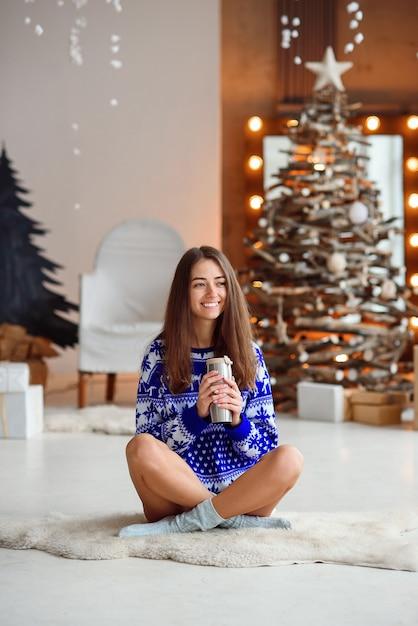 Een aantrekkelijk glimlachend meisje in een blauwe nieuwjaarssweater zit op een warm wit tapijt Premium Foto