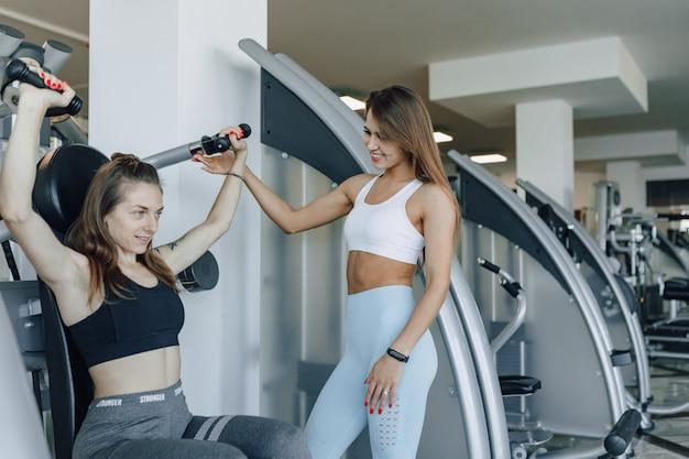 Een aantrekkelijk meisje in de sportschool schudt onder begeleiding van een trainer een bovenste groep spieren, armen en schouders. Premium Foto
