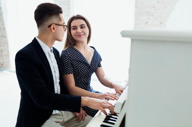 Een aantrekkelijke jonge paar het spelen piano die elkaar bekijkt Gratis Foto