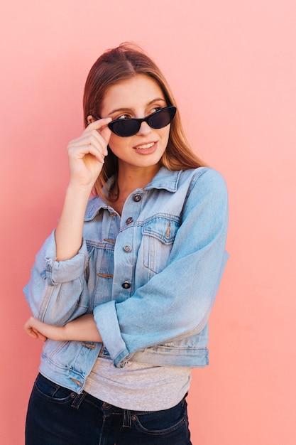 Een aantrekkelijke jonge vrouw die door oogglazen gluren die zich tegen perzikachtergrond bevinden Gratis Foto