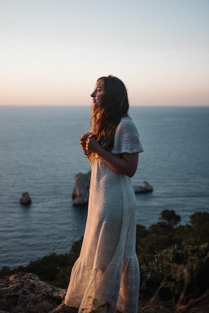 Een aantrekkelijke jonge vrouw met een mooie witte jurk die 's avonds langs de zee loopt Gratis Foto