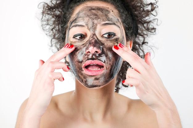 Een aantrekkelijke vrouw die zwart gezichtsmasker met haar vingers toepast tegen witte achtergrond Gratis Foto