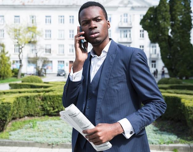 Een afrikaanse jonge krant die van de onderneemsterholding het in hand spreken op smartphone Gratis Foto